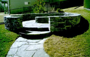 Circular Rundle Stone Retaining Wall, Raised Rundle Stone Patio, Rundle Stone Sidewalk & Brick BBQ Pit